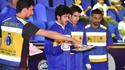 المحكم عبدالله القلاف مع مجموعة من الطلاب المشاركين في المسابقة